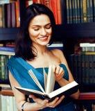 Muchacha musulmán morena adolescente joven en biblioteca entre cierre emocional de los libros encima del bookwarm, concepto sonri Foto de archivo libre de regalías