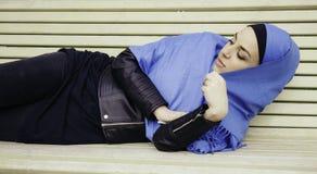 Muchacha musulmán mujer joven en una bufanda azul que miente en banco de parque foto de archivo libre de regalías