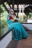 Muchacha musulmán que celebra el libro en el parque Fotografía de archivo