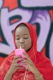 Muchacha musulmán que usa un smartphone y dos auriculares, doce años Imagen de archivo