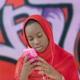Muchacha musulmán que usa un smartphone y dos auriculares, doce años Imagen de archivo libre de regalías