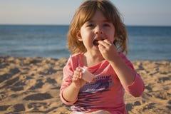 Muchacha muy bonita que come las patatas fritas y la salsa muchacha que se sienta en la arena en la playa contra el mar Foto de archivo