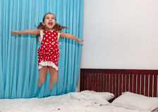 Muchacha muy feliz que salta en la cama Fotografía de archivo