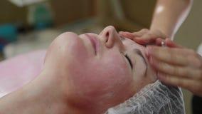 Muchacha muy hermosa que hace masaje facial en el salón del balneario Forma de vida sana almacen de metraje de vídeo