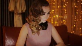 Muchacha muy hermosa y elegante en un café cerca de la ventana con la tableta almacen de video