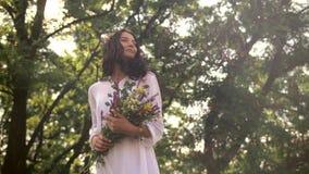 Muchacha natural de la belleza con el ramo de flores al aire libre en concepto del disfrute de la libertad metrajes