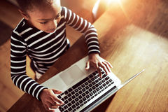Muchacha negra étnica joven que mecanografía en un ordenador portátil Fotografía de archivo libre de regalías