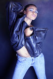 Muchacha negra adolescente atractiva que elimina de su chaqueta de cuero imagen de archivo