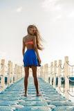 Muchacha negra adolescente hermosa en falda azul en el embarcadero plástico Fotos de archivo
