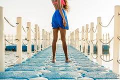 Muchacha negra adolescente hermosa en falda azul en el embarcadero plástico Fotos de archivo libres de regalías