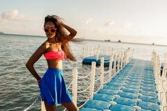Muchacha negra adolescente hermosa en falda azul en el embarcadero plástico Imagen de archivo libre de regalías