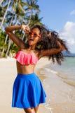Muchacha negra adolescente hermosa en falda azul y sujetador rosado en el b Fotos de archivo
