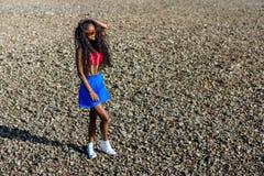 Muchacha negra adolescente hermosa en falda azul y sujetador rosado en el r Imagen de archivo