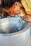 Muchacha negra adolescente hermosa en gafas de sol que bebe del agua d Imagen de archivo libre de regalías