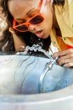 Muchacha negra adolescente hermosa en gafas de sol que bebe del agua d Imágenes de archivo libres de regalías
