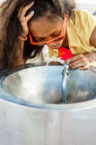 Muchacha negra adolescente hermosa en gafas de sol que bebe del agua d Fotografía de archivo