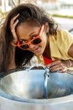 Muchacha negra adolescente hermosa en gafas de sol que bebe del agua d Foto de archivo libre de regalías