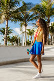 Muchacha negra adolescente hermosa en soporte azul de la falda con su smartp Imagenes de archivo