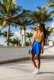 Muchacha negra adolescente hermosa en soporte azul de la falda con su smartp Fotografía de archivo libre de regalías