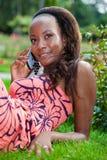 Muchacha negra adolescente que usa un teléfono Imágenes de archivo libres de regalías