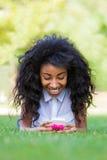 Muchacha negra adolescente que usa un teléfono, mintiendo en la hierba Fotos de archivo