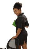 Muchacha negra agradable con un cuaderno y la pluma Fotografía de archivo