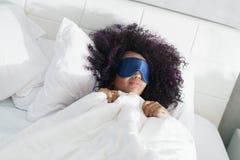 Muchacha negra cansada que despierta en cama con la máscara del sueño Fotografía de archivo libre de regalías