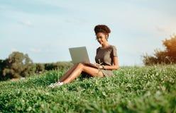 Muchacha negra con el ordenador portátil que se sienta en la hierba Imagen de archivo libre de regalías