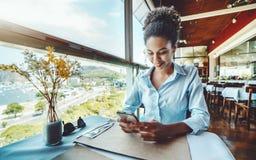 Muchacha negra con el smartphone que espera en café de lujo Imagen de archivo libre de regalías