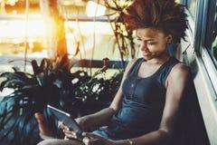 Muchacha negra con la tableta digital que se sienta en el pórtico Imagen de archivo