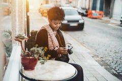 Muchacha negra con photocamera del vintage en la calle Foto de archivo