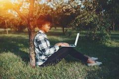 Muchacha negra de risa en parque con el ordenador portátil Foto de archivo libre de regalías