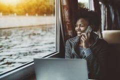 Muchacha negra de risa que habla en el teléfono en nave Fotografía de archivo