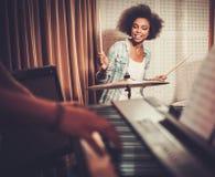 Muchacha negra detrás de los tambores en un ensayo Fotos de archivo