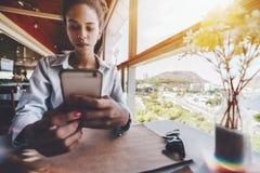 Muchacha negra en café que charla en el teléfono móvil cerca de ventana Imágenes de archivo libres de regalías