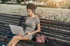 Muchacha negra en el banco de parque con el netbook Imagen de archivo