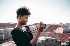 Muchacha negra en el tejado con la cámara de la foto del vintage Fotos de archivo libres de regalías