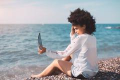 Muchacha negra en la playa que toma el selfie Imagenes de archivo