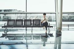 Muchacha negra en sala de espera del ferrocarril con smartphone Fotografía de archivo