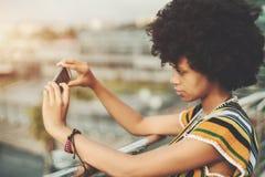 Muchacha negra encantadora con el pelo del disco que hace piture en el teléfono móvil Fotos de archivo