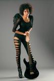Muchacha negra hermosa con las alas del ángel y la guitarra eléctrica foto de archivo libre de regalías