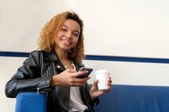 Muchacha negra hermosa joven en una blusa blanca y una chaqueta de cuero con un vidrio de café que se sienta en un sofá azul en e Imagenes de archivo