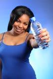Muchacha negra joven feliz que sostiene hacia fuera el agua embotellada Imagenes de archivo