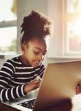 Muchacha negra joven que charla alguien usando el ordenador portátil Imagen de archivo libre de regalías