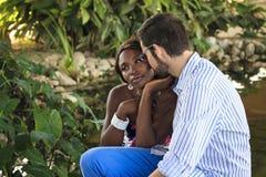 Muchacha negra joven y hombre blanco junto en el jardín Fotos de archivo