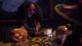 Muchacha negra linda en la máscara del diablo que asusta a su amigo el la noche de Halloween metrajes