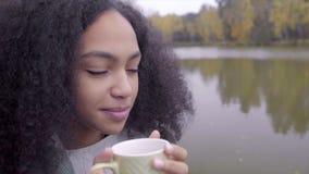 Muchacha negra linda que se envuelve en tela escocesa de lana y que bebe té caliente almacen de metraje de vídeo