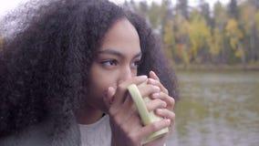 Muchacha negra linda que se envuelve en tela escocesa de lana y que bebe té caliente almacen de video