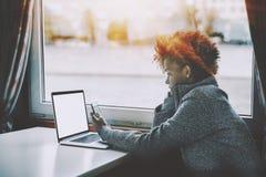 Muchacha negra pensativa con smartphone y ordenador portátil en la nave Imagen de archivo
