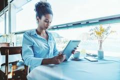 Muchacha negra pensativa del freelancer en restaurante con el tabl digital Fotos de archivo libres de regalías